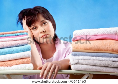 An upset woman sitting at heaps of ironed towels