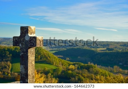 Ancient catholic cross in stone on a hill with countryside in the background, France