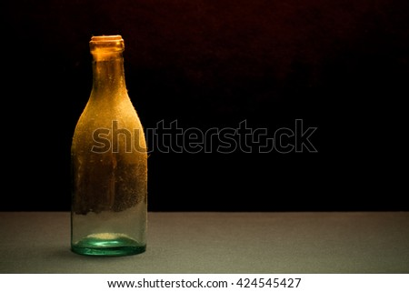 Ancient dust bottle on dark background. Selective focus. Shallow depth of field. Toned.