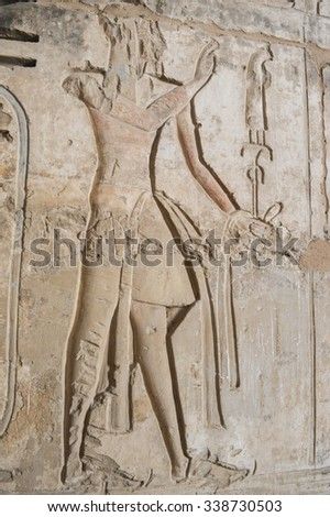 Ancient Egyptian hieroglyphic carvings on a temple wall at Medinat Habu in Luxor