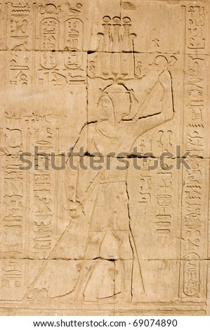 Ancient Egyptian pharaoh killing evil in the form of a snake.  Temple of Horus, Edfu, Egypt.