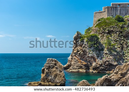Ancient fortress on the rock. Stone tower and walls of the fortress. Ancient fortress on the top of the mountain. Fortress against the bright sky.