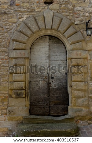 Ancient wooden door in a village of the Tuscan countryside