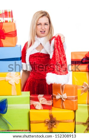 Angry Christmas woman holding Santa hat, surrounded by presents, isolated on white background.