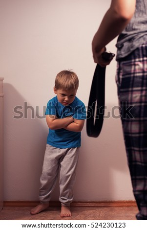 Angry mother with belt and little child in corner. Domestic violence, aggression on the family. Abuse against children.