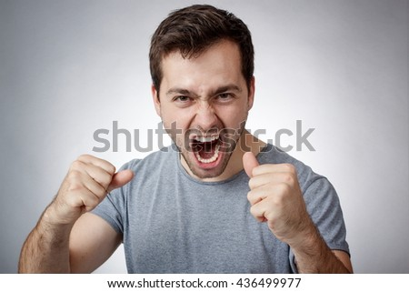 Angry young man clutching fists and shouting