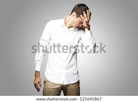 Angry young man doing frustration gesture over grey background