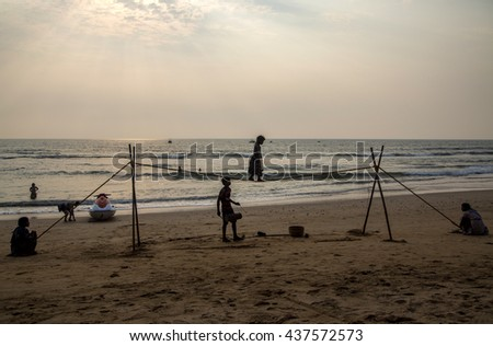 ANJUNA, INDIA - OCTOBER 14, 2015: Unidentified Goan Girl on a tightrope at the Anjuna Beach. Small groups of entertainers travel along the coast and give free shows for tourists on the beach.