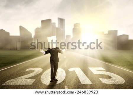 Anonymous businessman with blindfolded walking on the road with numbers 2015