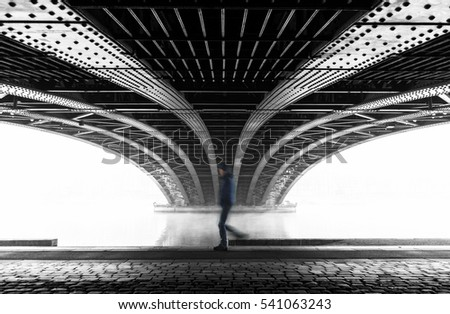 Anonymous man walking under a bridge in Lyon on a foggy winter day. With motion blur and shallow focus.
