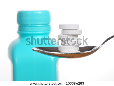 Antacid tablets on a spoon, a bottle of antacid blurred in the background