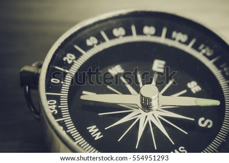 Antique grunge compass with needle pointing the North and South direction, selective focus and shallow depth of field. Abstract concept of style and filtered process.