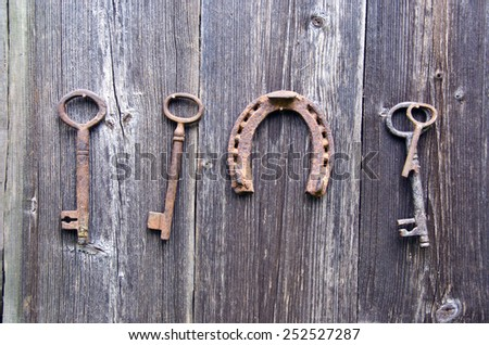 antique rusty key and luck symbol horseshoe on old wooden farm wall