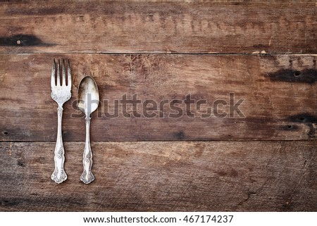 Antique silverware spoon and fork over a rustic old wood table top background. Image shot from overhead.