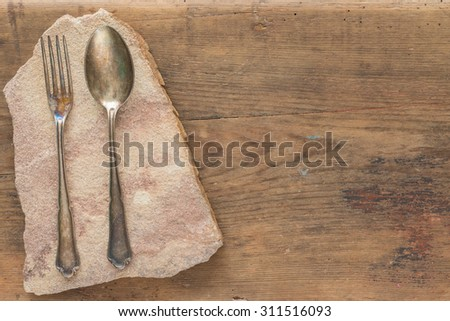 antique spoon and fork on sandstone slab on wooden background