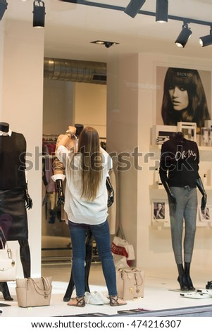ANTWERP, BELGIUM - JULY 6, 2015: A young woman prepare showcase in a store selling women's clothing.