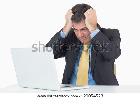 Anxious businessman sitting at his desk with a laptop on a white background