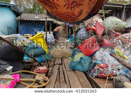 AO SALAD, THAILAND, JANUARY 31, 2016 : A man is selecting recyclable stuff at home in the AO Salad fishing village in Ko Kood Island, Thailand