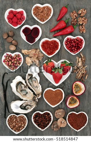 Aphrodisiac food selection with foods in porcelain heart shaped bowls and loose on marble background.