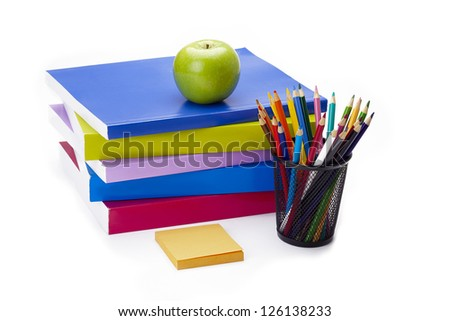 Apple sitting on top of stack of books with a sticky note and set of coloring pencil close by.