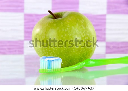 Apple with a toothbrush on shelf in bathroom