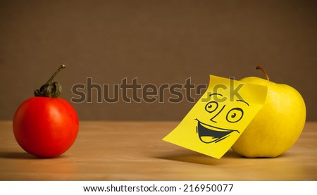 Apple with sticky post-it note looking happy at tomato