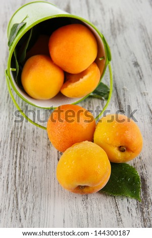 Apricots in bucket on wooden table