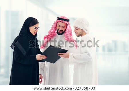 Arab business people in a meeting, three business people standing in a modern office interior discussing work, ethnic business people, business team.