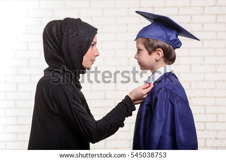 Arabic mother and son are preparing to graduation ceremony.