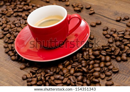 Arabica coffee beans and red espresso mug on a wooden table