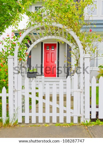 Arch wooden entrance with the fence, cowered with flowers