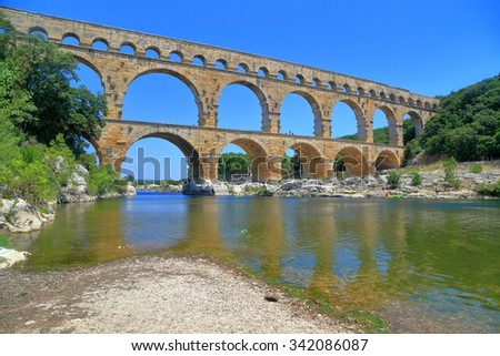 Arches of Pont du Gard across a river near Nimes, France