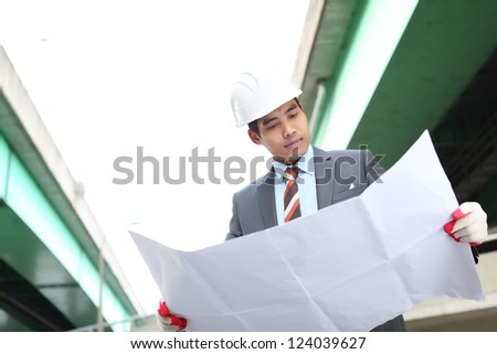 architect checking a drawing  on highway construction site
