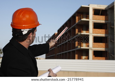 Architect wearing a protective helmet pointing to building.
