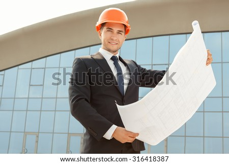 Architect wearing hardhat inspecting the blueprints outdoors