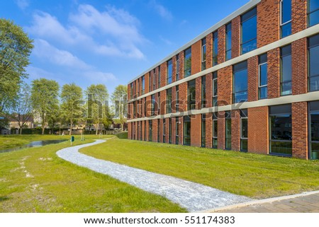 Architecture detail of school situated next to park with walking trail on a bright day in spring