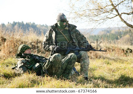 Armed soldier in camouflage is resting after the patrol.