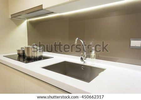 Arranged kitchen pot and kitchen sink on kitchen cabinet