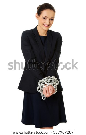 Arrested businesswoman with handcuffs around hands.