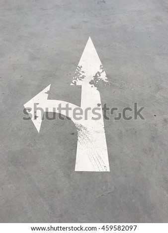 Arrow on the road pointing in two directions.