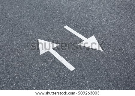 Arrow signs on asphalt road showing direction of movement, close up