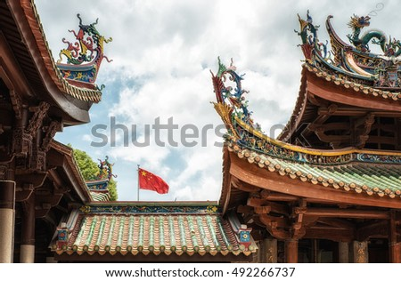 Art of Chinese temple roof with chinese flag in the background