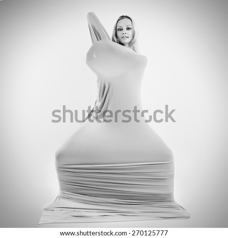 Art photo of a women silhouette breaking through the fabric.  Black and white photo