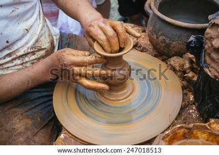 artisan potter molding a piece of clay on a lathe
