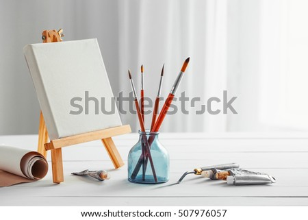 Artistic paintbrushes, canvas on easel, tubes of oil paint, palette knife on white wooden desk.