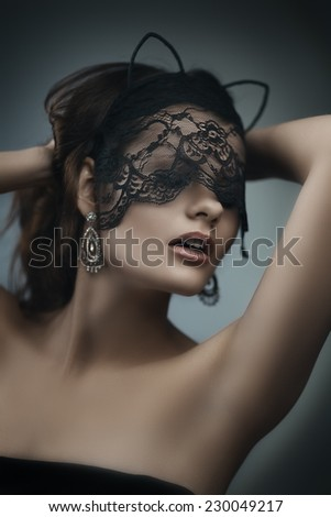Artistic portrait of young beautiful brunette woman in lace mask. Shallow depth of field