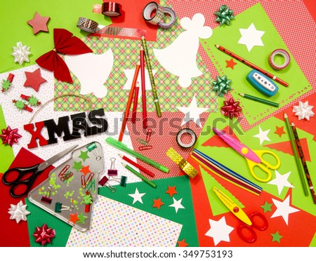 Arts and craft supplies for Christmas. Red and green color paper, pencils, different washi tapes, craft scissors, cardboard cuts, festive Xmas supplies for decoration.