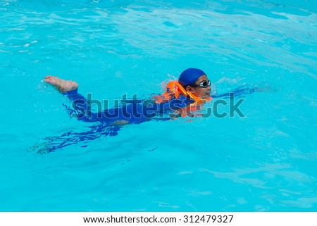 Asia boy swimming in the blue pool.