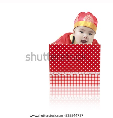 Asian baby cute and smile wearing Chinese suit or clothes with hat playing and emerged from the open red gift box for surprise on Chinese happy new year day, isolated on white background