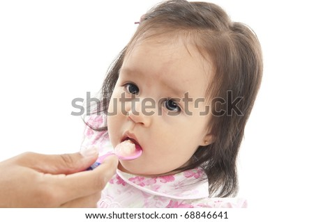 Asian Baby eating with a spoon .